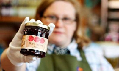 A woman in an apron hold out a jar of Raspberry Jam
