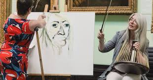 Tanya Raabe-Webber sketcheing Dame Evelyn Glennie who has a percussion instrument on her lap and a violin bow in her hand