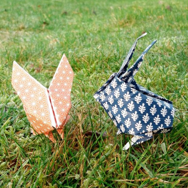 2 origami rabbits sitting on the grass