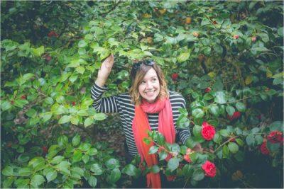 Smiling Casia in a large red rosebush/ Casia yn gwenu mewn llwyn rhosod coch