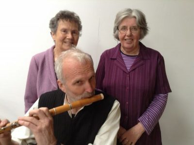 Photo of Marlis and Delma behind Andy Warren playing the flute/ Llun o Marlis, Delma, Andy