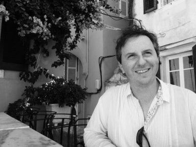 a black and white photo of a smiling Gregory Leadbetter/Llun du a gwyn o Gregory Leadbetter yn gwenu