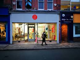 Photo of a person in the dark walking past JOLT shop in Oswestry which is full of light and invitation