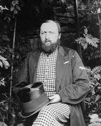 a black and white photo of a bearded man in what looks like pyjamas and holding a top hat/ Llun du a gwyn o ddyn barfog yn gwysgo pyjamas ac yn dal het uchel