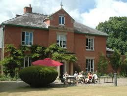 A red brick old grand house with people at tables outside/Pobl yn eistedd wrth fyrddau o flaen ty hynafol o frics coch
